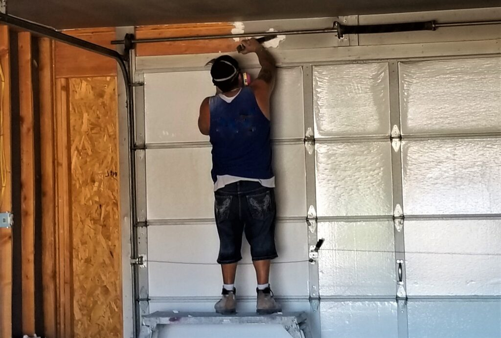 Construction Worker Installing a Roll Up Garage Door in a Garage.
