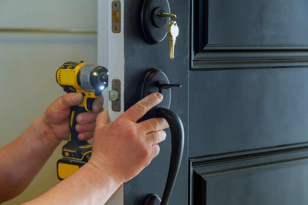 Closeup of a professional locksmith installing a new lock on a house exterior door with the inside
