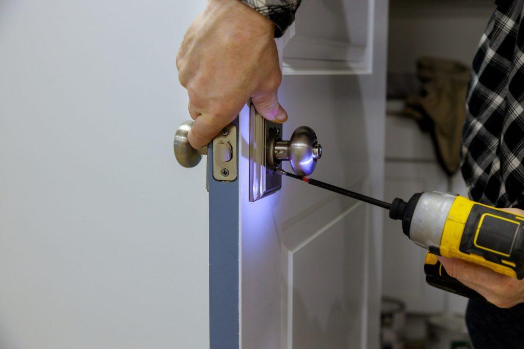 Maintenance in the apartment woodworker hands is installing the doors handle