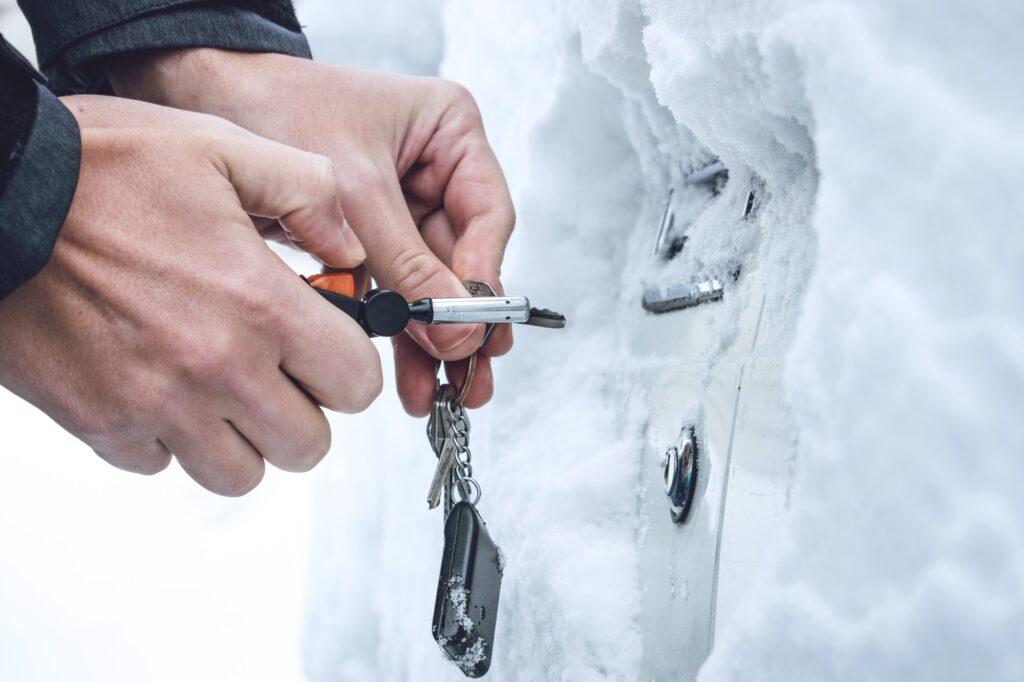 Ways to Open Frozen Car Doors. heating up the key. Male hand opening winter car door with keys